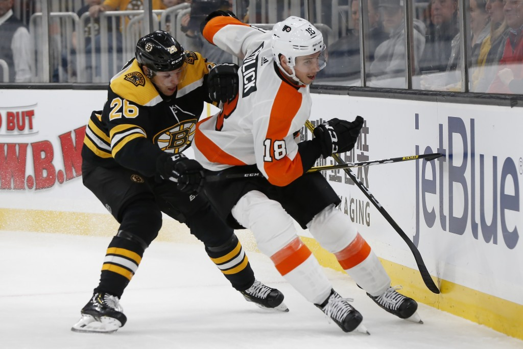 Boston Bruins' Par Lindholm (26) and Philadelphia Flyers' Tyler Pitlick (18) battle along the boards during the first period of an NHL hockey game in ...