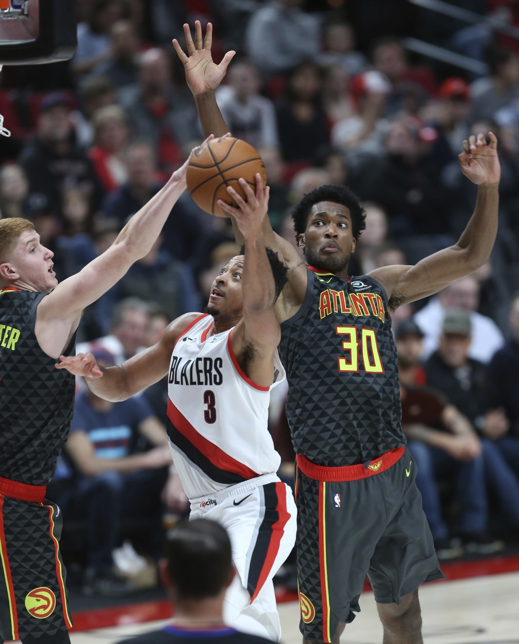 Portland Trail Blazers guard CJ McCollum, center, shoots between Atlanta Hawks guard Kevin Huerter, left, and center Damian Jones, right, during the f...