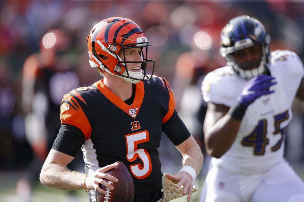 Cincinnati Bengals quarterback Ryan Finley (5) looks to pass under pressure from Baltimore Ravens linebacker Jaylon Ferguson (45) during the first hal...