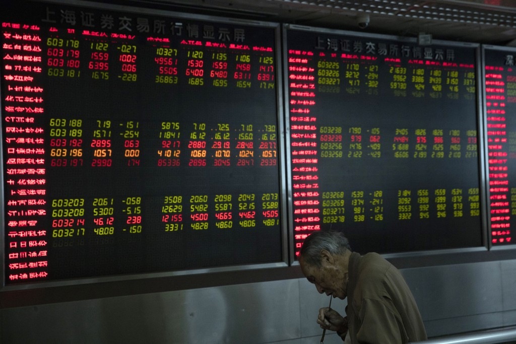 An investor eats a meal near a board displaying stock prices at a brokerage in Beijing Monday, Nov. 11, 2019. Shares declined Monday in Asia as invest...