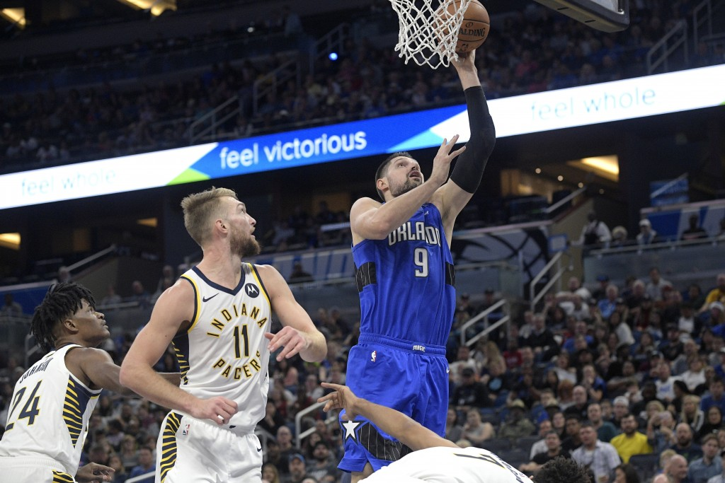 Orlando Magic center Nikola Vucevic (9) goes up for a shot in front of Indiana Pacers forward Alize Johnson (24), forward Domantas Sabonis (11) and gu...
