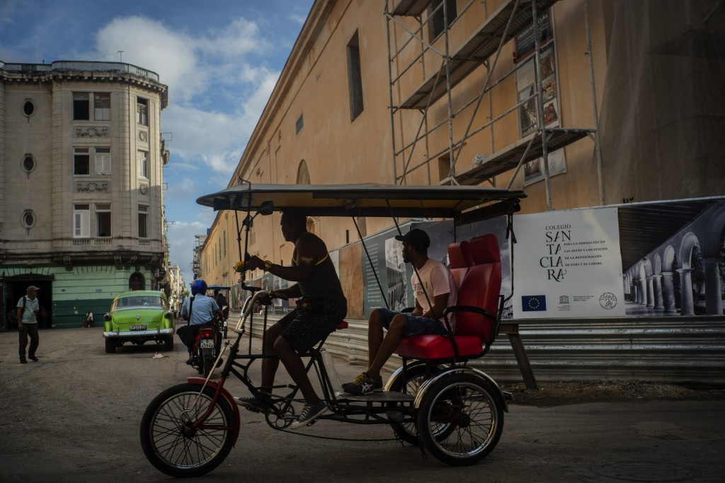 In this Nov. 9, 2019 photo, a bicycle taxi driver navigates his client past buildings under restoration in Havana, Cuba. The city will celebrate its 5...