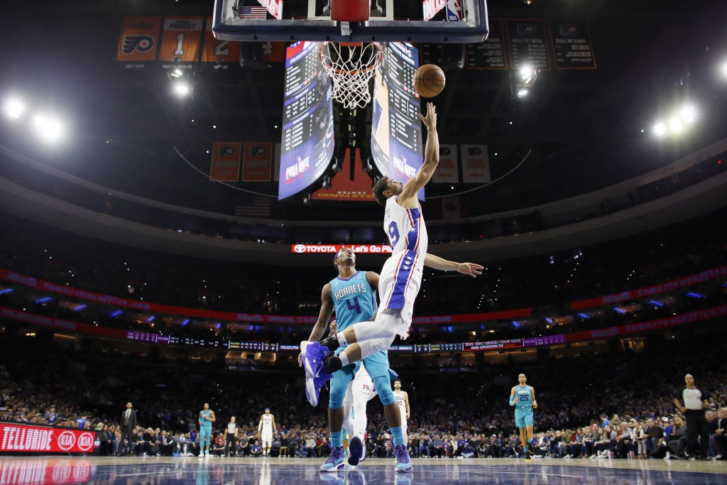 Philadelphia 76ers' Raul Neto, right, goes up for a shot in front of Charlotte Hornets' Devonte' Graham during the first half of an NBA basketball gam...