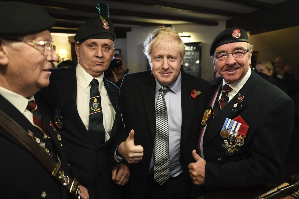 Britain' Prime Minister Boris Johnson, centre, meets with military veterans at the Lych Gate Tavern in Wolverhampton, England, Monday, Nov. 11, 2019 a...