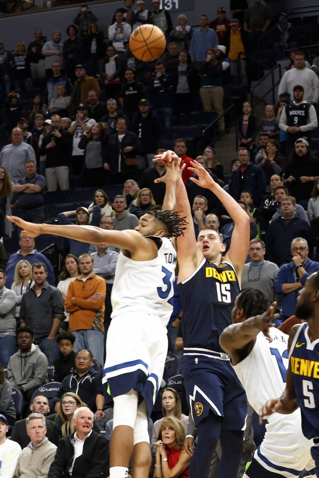 Denver Nuggets' Nikola Jokic, right, of Serbia, shoots the go-ahead basket over Minnesota Timberwolves' Karl-Anthony Towns in the final seconds in ove...