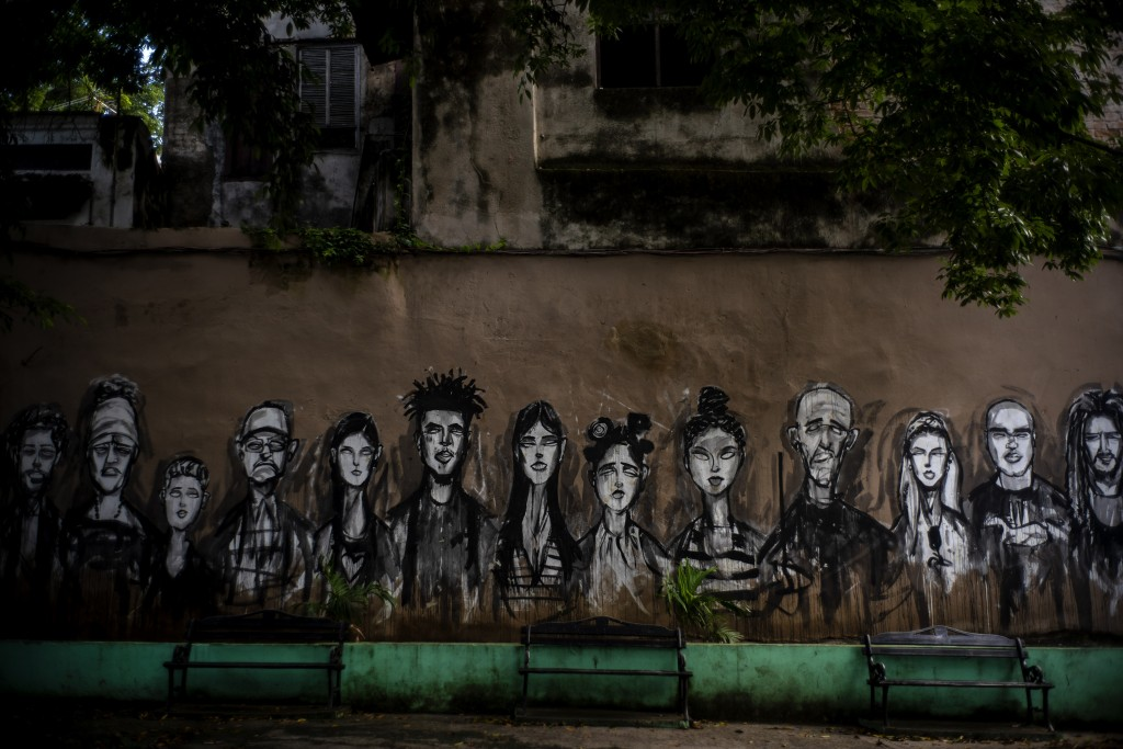 In this Nov. 10, 2019 photo, a wall is covered by a mural of faces, representing local residents, in a plaza in Old Havana, Cuba. The city will celebr...
