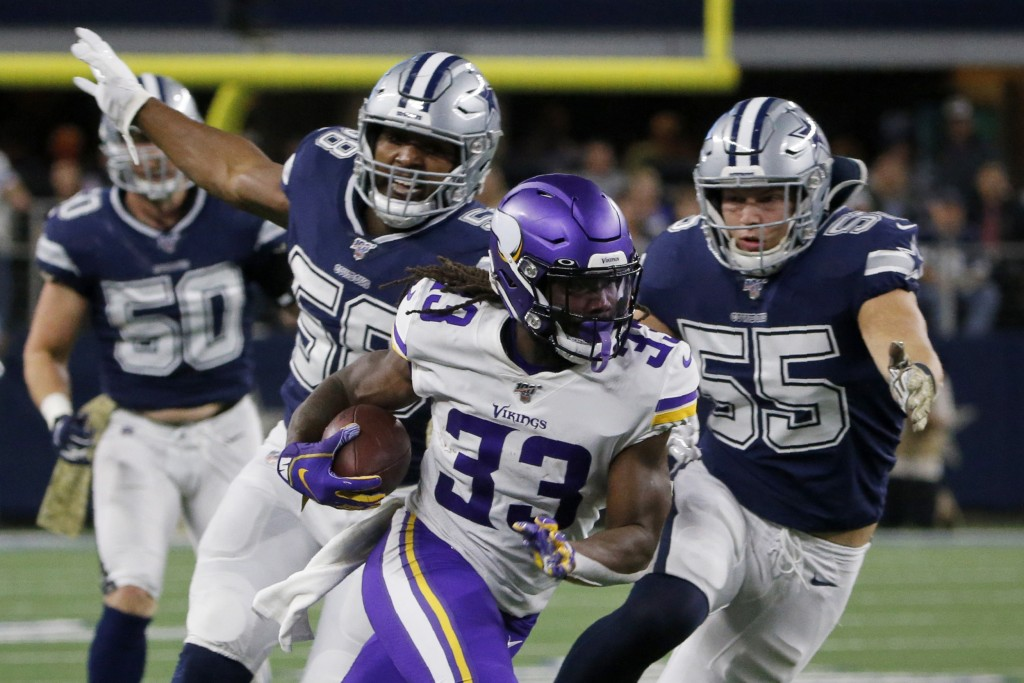 Minnesota Vikings running back Dalvin Cook (33) runs the ball as Dallas Cowboys' Robert Quinn (58) and Leighton Vander Esch (55) give chase during the...