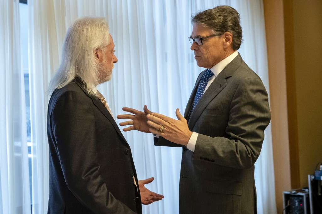 In this Nov. 12, 2018, photo provided by the U.S. Embassy in Kyiv, Energy Secretary Rick Perry talks with Michael Bleyzer during a speech in Kyiv, Ukr...