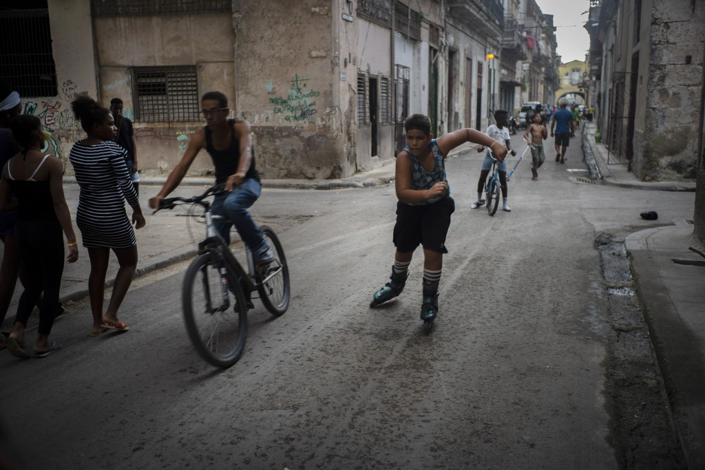 In this Nov. 9, 2019 photo, a youth rollerblades amid cyclists and pedestrians in Old Havana, Cuba. The city will celebrate its 500th anniversary on N...