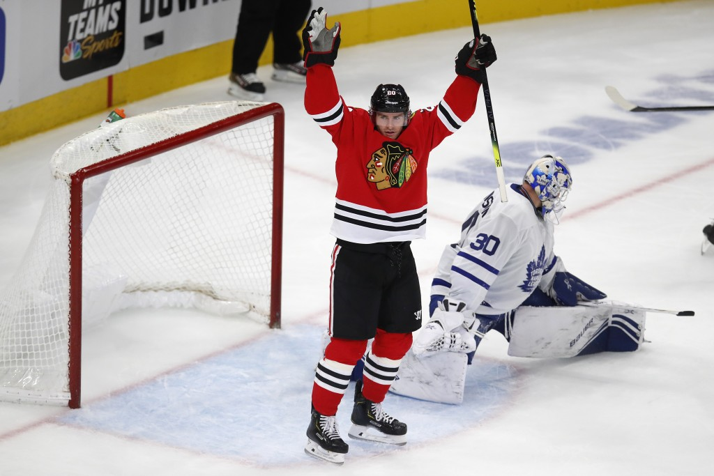 Chicago Blackhawks' Brandon Saad, left, celebrates his goal on Toronto Maple Leafs' Michael Hutchinson during the third period of an NHL hockey game S...