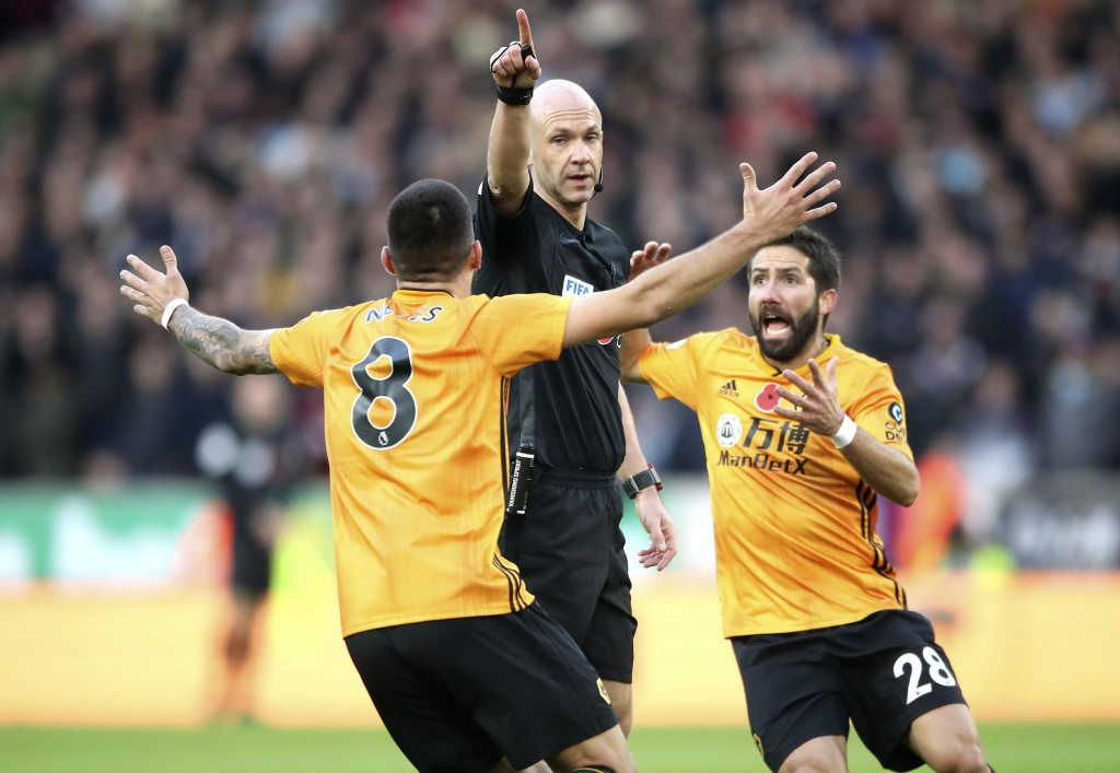 Wolverhampton Wanderers' Ruben Neves, left and Joao Moutinho, right, appeal to referee Anthony Taylor, during the English Premier League soccer match ...