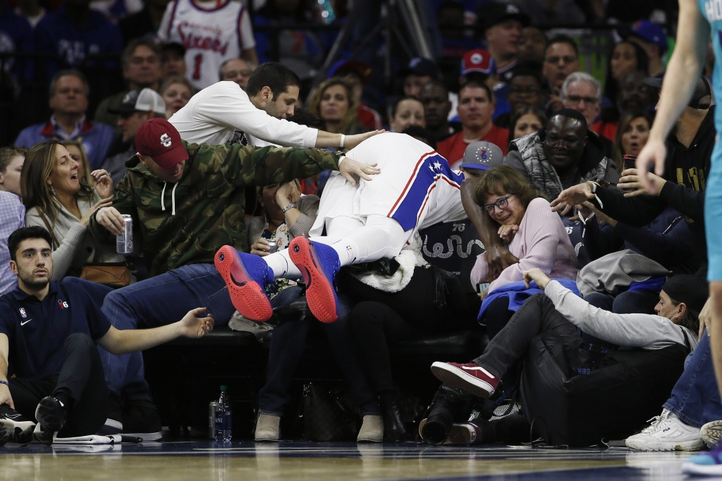 Philadelphia 76ers' Joel Embiid dives into the seats for a loose ball during the first half of the team's NBA basketball game against the Charlotte Ho...