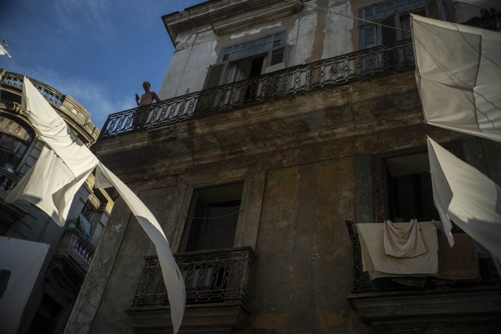 In this Nov. 9, 2019 photo, a man stands on the balcony of his home amid drying sheets in Havana, Cuba. The city of Havana will celebrate its 500th an...