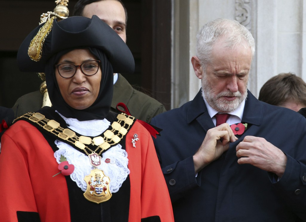 Britain's main opposition Labour Party leader Jeremy Corbyn adjusts his poppy, as he waits outside Islington Town Hall with Islington's Mayor Rakhia I...