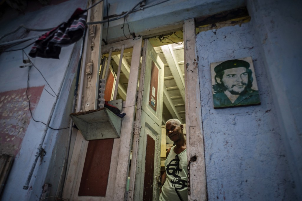 "In this Nov. 10, 2019 photo, Lorenzo Ballester poses at the door of his house, decorated with a photo of revolutionary hero Ernesto ""Che"" Guevara, in ..."