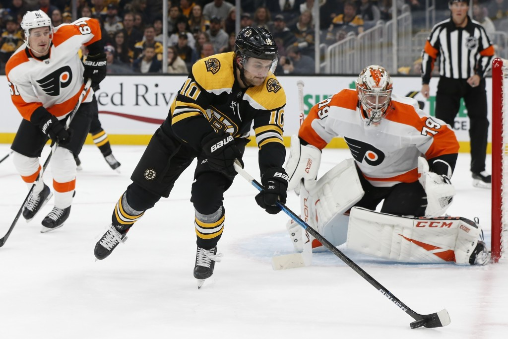 Boston Bruins' Anders Bjork (10) controls the puck in front of Philadelphia Flyers' Carter Hart (79) during the first period of an NHL hockey game in ...