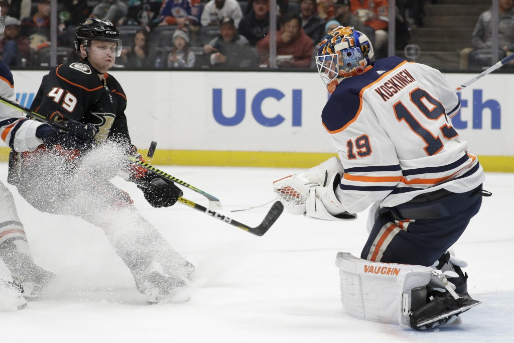 Edmonton Oilers goaltender Mikko Koskinen, right, blocks a shot by Anaheim Ducks left wing Max Jones during the second period of an NHL hockey game in...