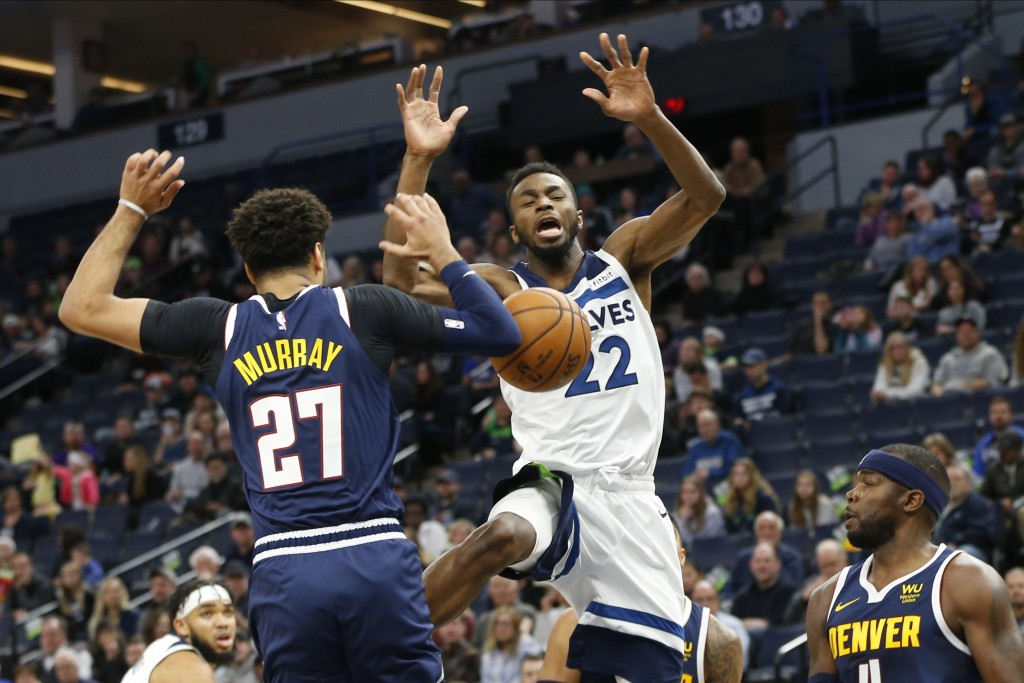 Minnesota Timberwolves' Andrew Wiggins, center, loses the ball as Denver Nuggets' Jamal Murray, left, and Paul Millsap defend in the first half of an ...