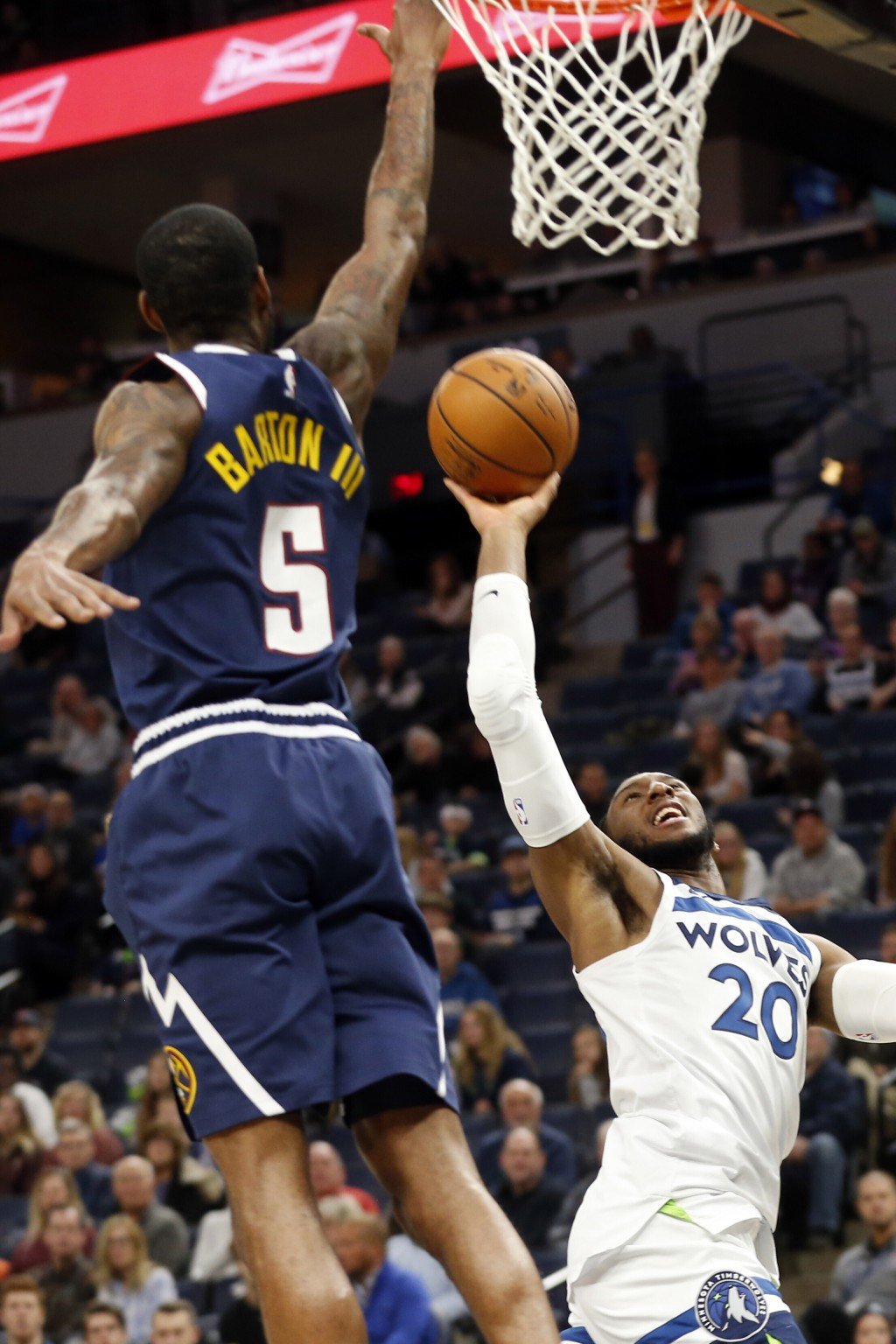 Minnesota Timberwolves' Josh Okogie, right, of Nigeria, goes for a layup as Denver Nuggets' Will Barton defends in the first half of an NBA basketball...