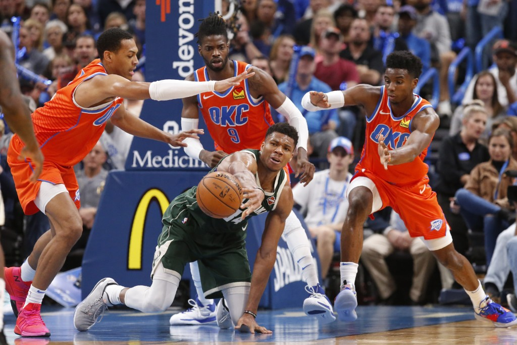 Milwaukee Bucks forward Giannis Antetokounmpo passes the ball away from Oklahoma City Thunder forward Darius Bazley, left, forward Nerlens Noel (9) an...