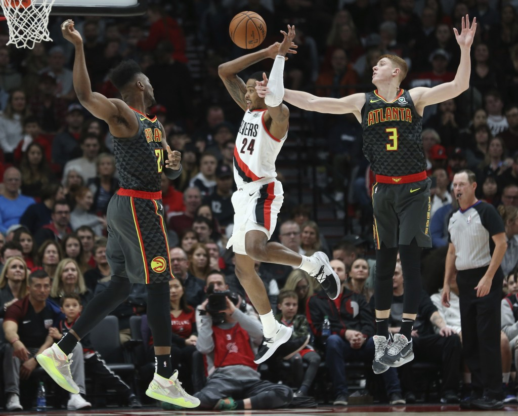 Portland Trail Blazers guard Kent Bazemore, center, is fouled by Atlanta Hawks guard Kevin Huerter, right, as forward Bruno Fernando defends during th...