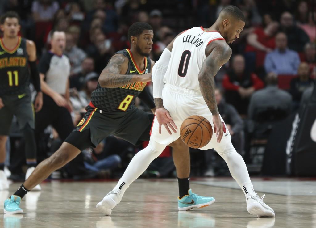 Portland Trail Blazers guard Damian Lillard, right, dribbles around Atlanta Hawks guard Tyrone Wallace during the first half of an NBA basketball game...