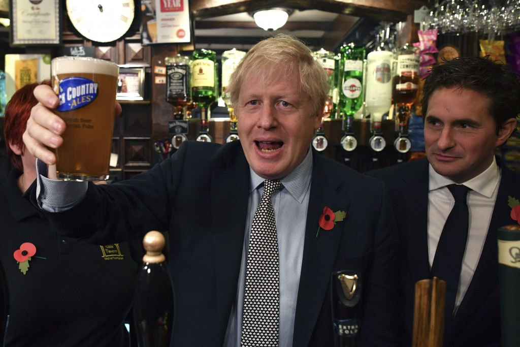 Britain' Prime Minister Boris Johnson raises a pint of beer, as he meets with military veterans at the Lych Gate Tavern in Wolverhampton, England, Mon...