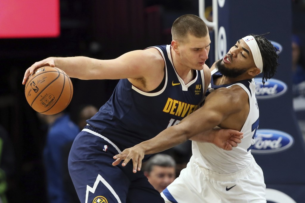 Denver Nuggets' Nikola Jokic, left, of Serbia, keeps the ball at arm's length from Minnesota Timberwolves' Karl-Anthony Towns in the first half of an ...