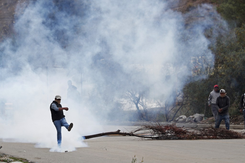 A man kicks a tear gas canister during clashes between police and supporters of former President Evo Morales who set up barricades in La Paz, Bolivia,...