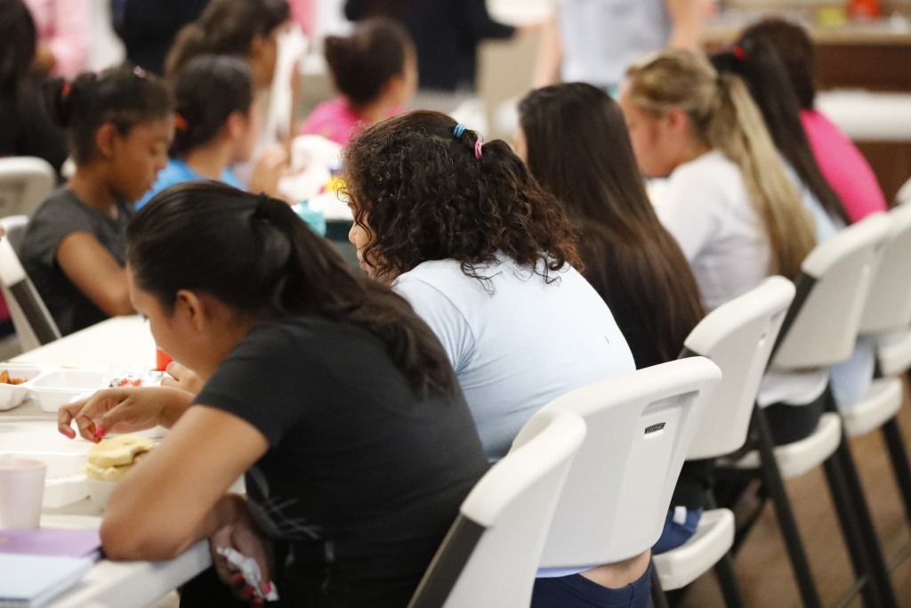 In this Sept. 24, 2019 photo, girls eat lunch at a shelter for migrant teenage girls, in Lake Worth, Fla. The nonprofit U.S. Committee for Refugees an...