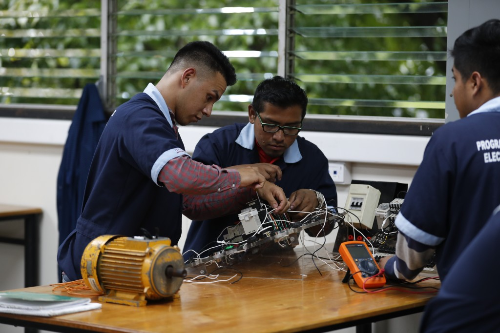 In this Oct. 11, 2019, photo, José Fernando Guillén Rodríguez, 21, left, practices building circuits with other students around a workbench in San Sal...