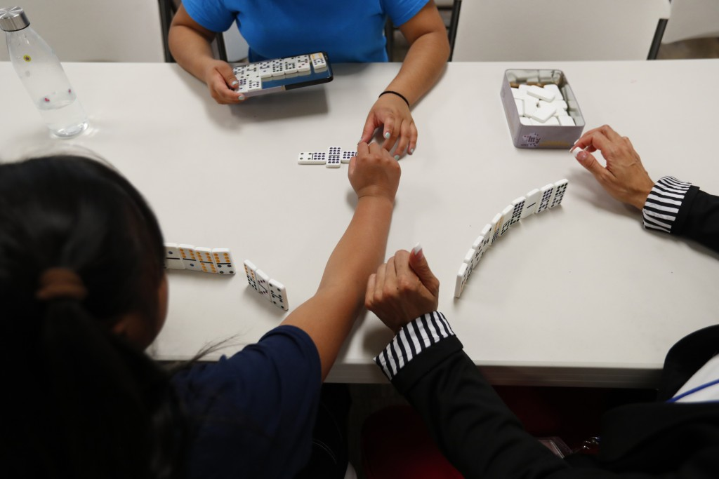 In this Sept. 24, 2019, photo, girls play dominos with a staff member at a shelter for migrant teenage girls, in Lake Worth, Fla. The nonprofit U.S. C...