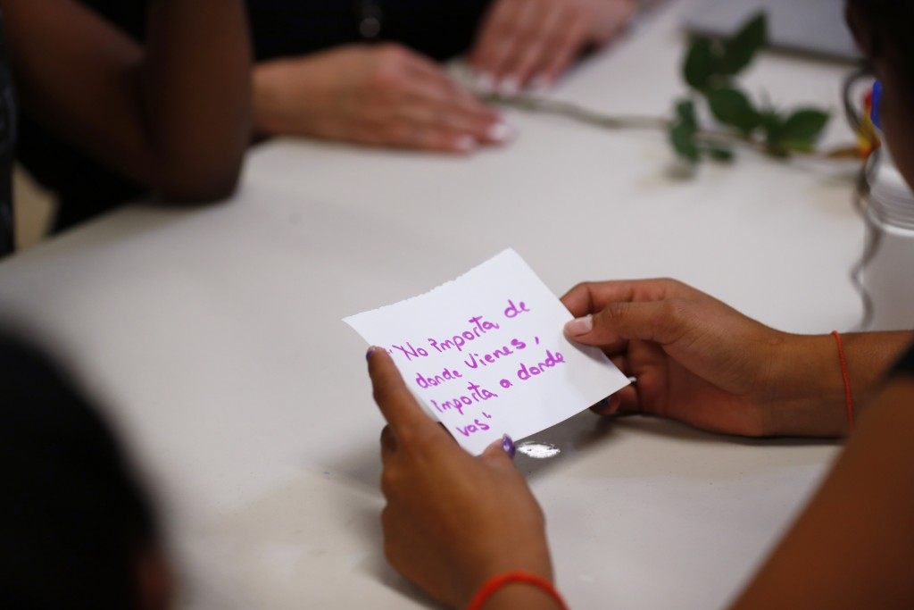 "In this Sept. 24, 2019, photo, a migrant girl in U.S. government custody holds a card that says, in Spanish, ""It doesn't matter where you come from, i..."