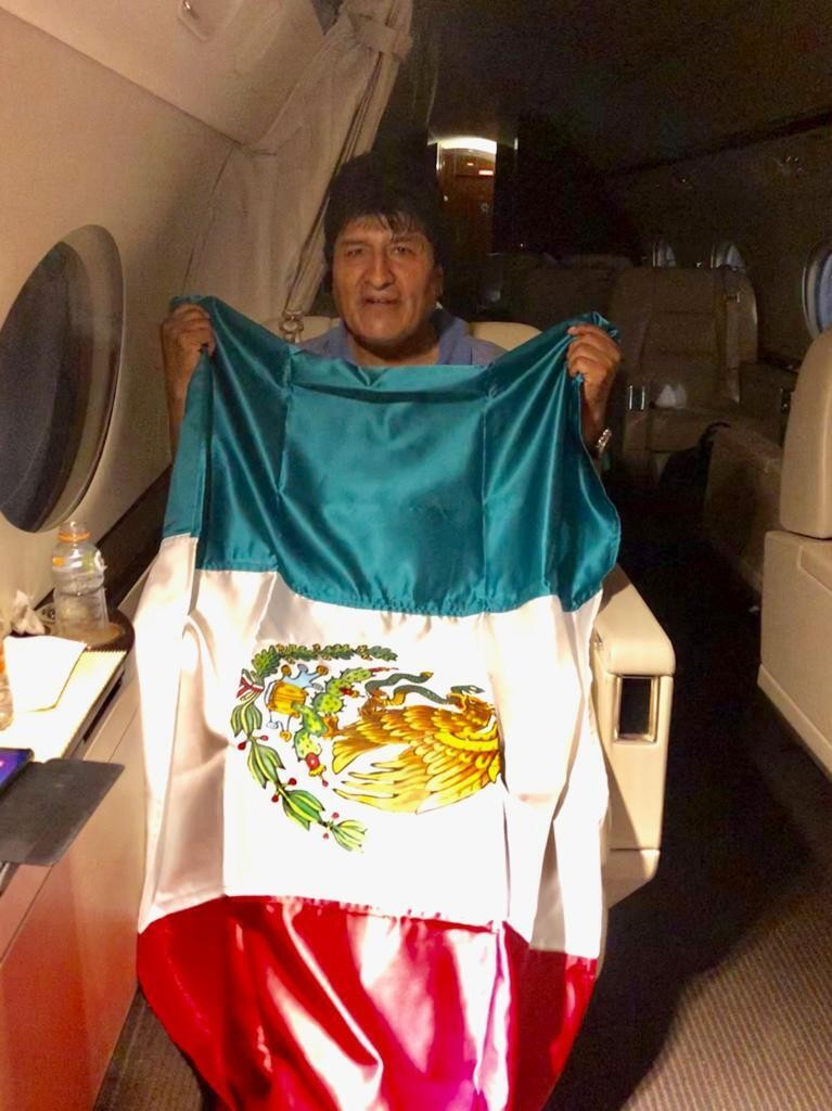 This photo released by by Mexico's Foreign Minister Marcelo Ebrard shows Bolivia's former President Evo Morales holding a Mexican flag aboard a Mexica...