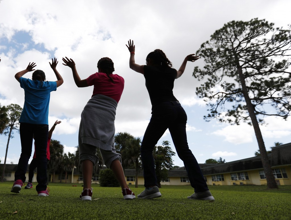 FILE - In this Sept. 24, 2019, file photo, girls dance as they do exercises at a shelter for migrant teenage girls, in Lake Worth, Fla. The nonprofit ...
