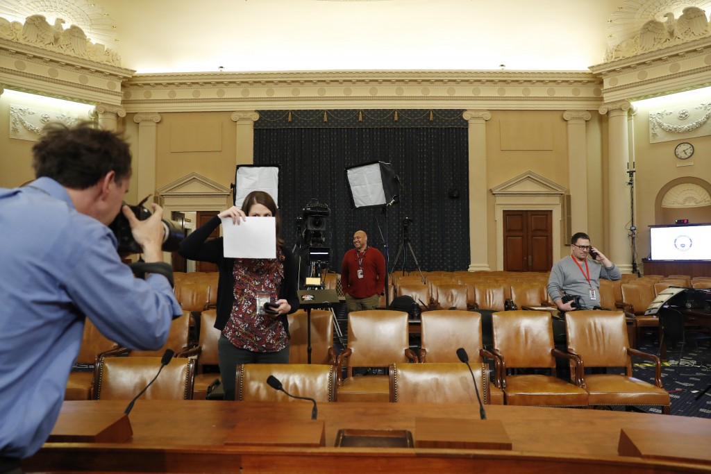 A photographer sets a white balance in the hearing room where the House will begin public impeachment inquiry hearings Wednesday, on Capitol Hill in W...