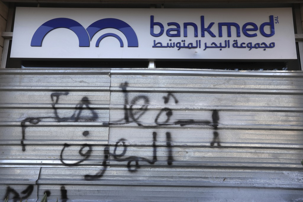 """A door of a closed bank is spray painted with a message in Arabic that reads, """"Down with the rule of the banks,"""" in Beirut, Lebanon, Tuesday, Nov. 12,..."""