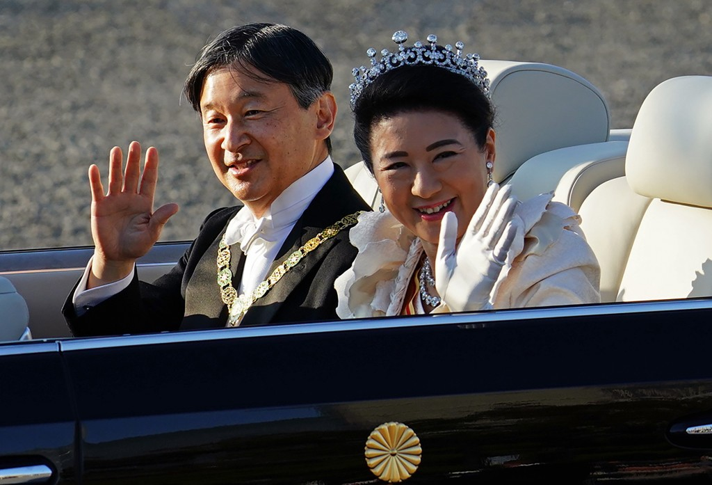 FILE - In this Nov. 10, 2019, file photo, Japan's Emperor Naruhito, left, and Empress Masako, wave during the royal motorcade in Tokyo. Emperor Naruhi...