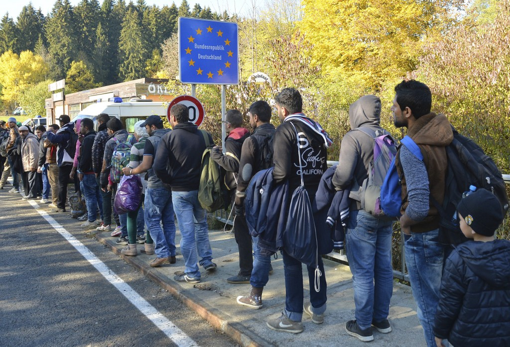 FILE - In this Wednesday, Oct. 28, 2015 file photo German federal police officers guide a group of migrants on their way after crossing the border bet...
