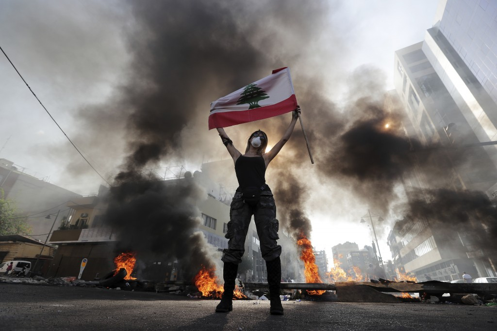 An anti-government protester holds a Lebanese flag while standing in front burning tires that block a road in the town of Jal el-Dib, north of Beirut,...