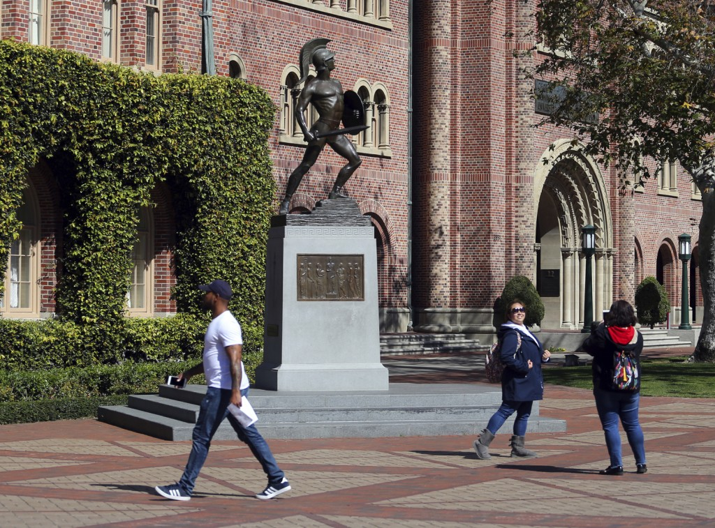 FILE - In this March 12, 2019, file photo, people pose for photos in front of the iconic Tommy Trojan statue on the campus of the University of Southe...