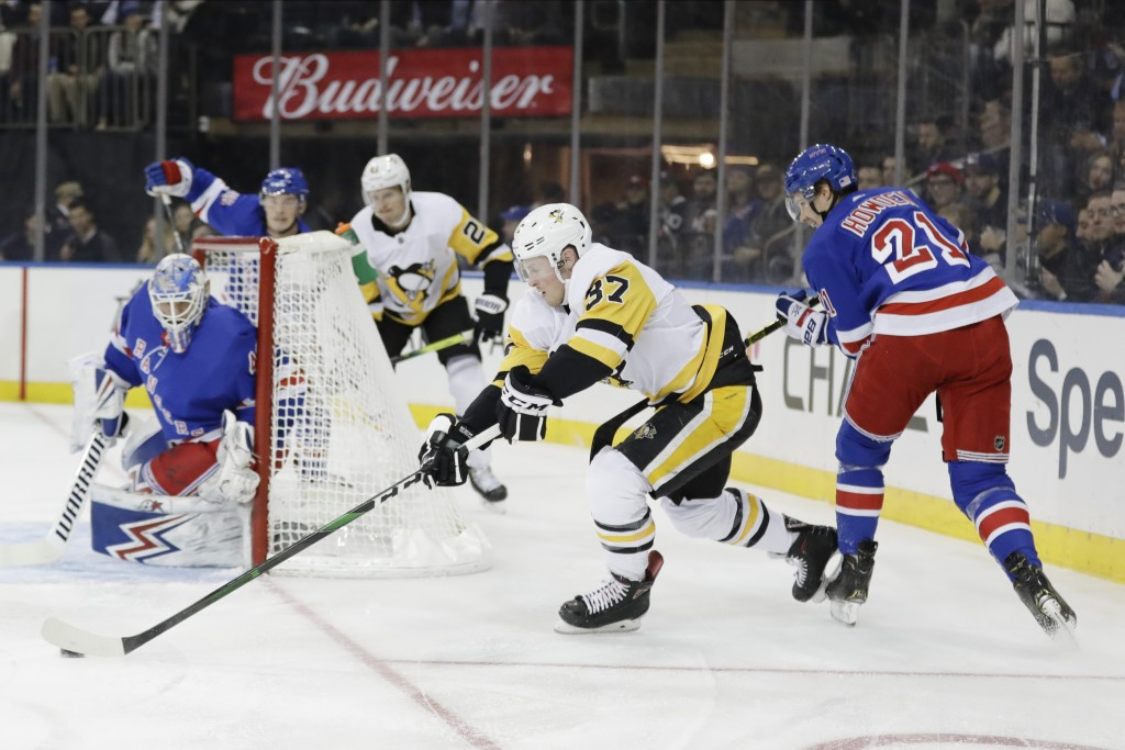 Pittsburgh Penguins' Sam Lafferty (37) gets control of the puck from New York Rangers' Brett Howden (21) during the first period of an NHL hockey game...