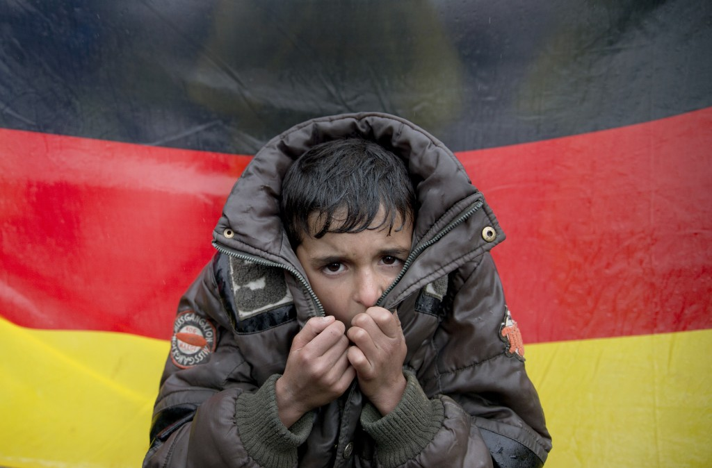 FILE - In this Wednesday, March 9, 2016 file photo a child tries to warm his hands, backdropped by Germany's flag as protesting migrants stage a sit i...