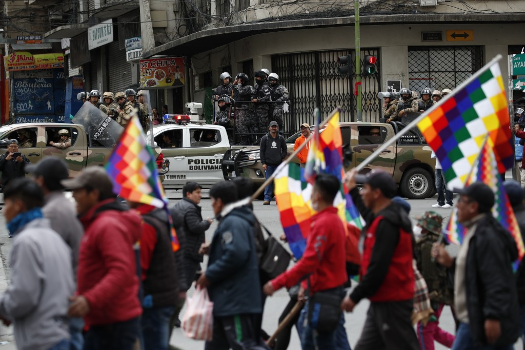 Police patrol on the sidelines of a march by supporters of former President Evo Morales, arriving from El Alto and entering La Paz, Bolivia, Tuesday, ...
