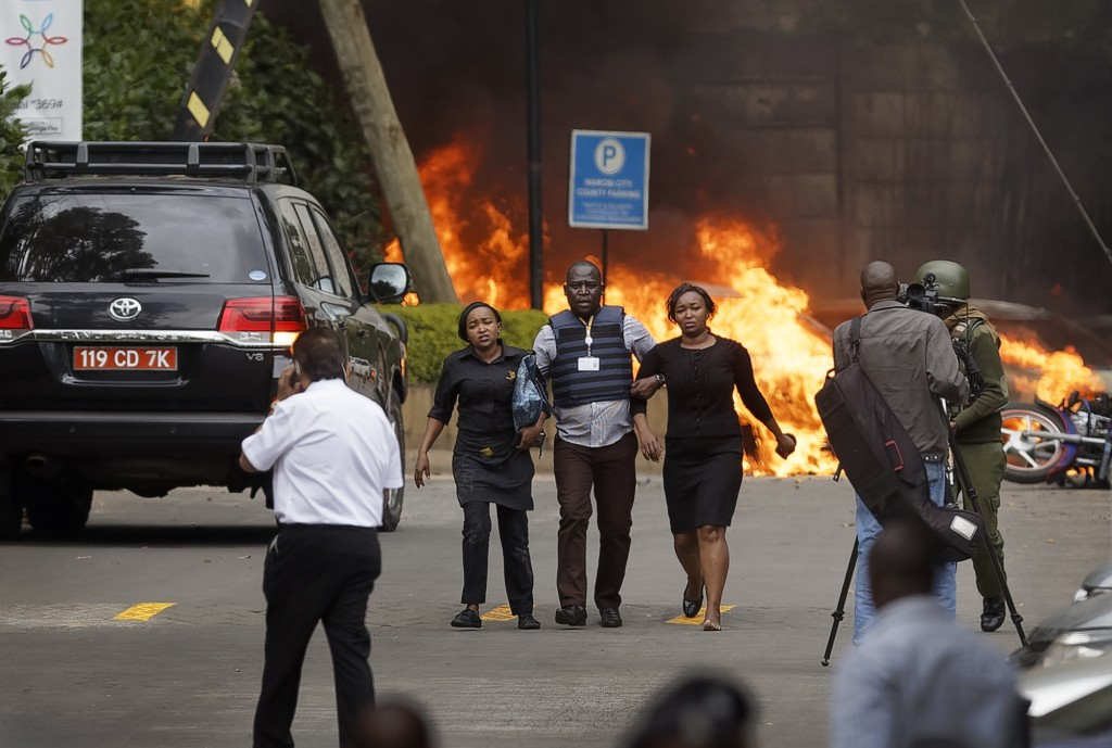 FILE - In this Tuesday, Jan. 15, 2019 file photo, security forces help civilians flee the scene as cars burn behind, at a luxury hotel complex attacke...