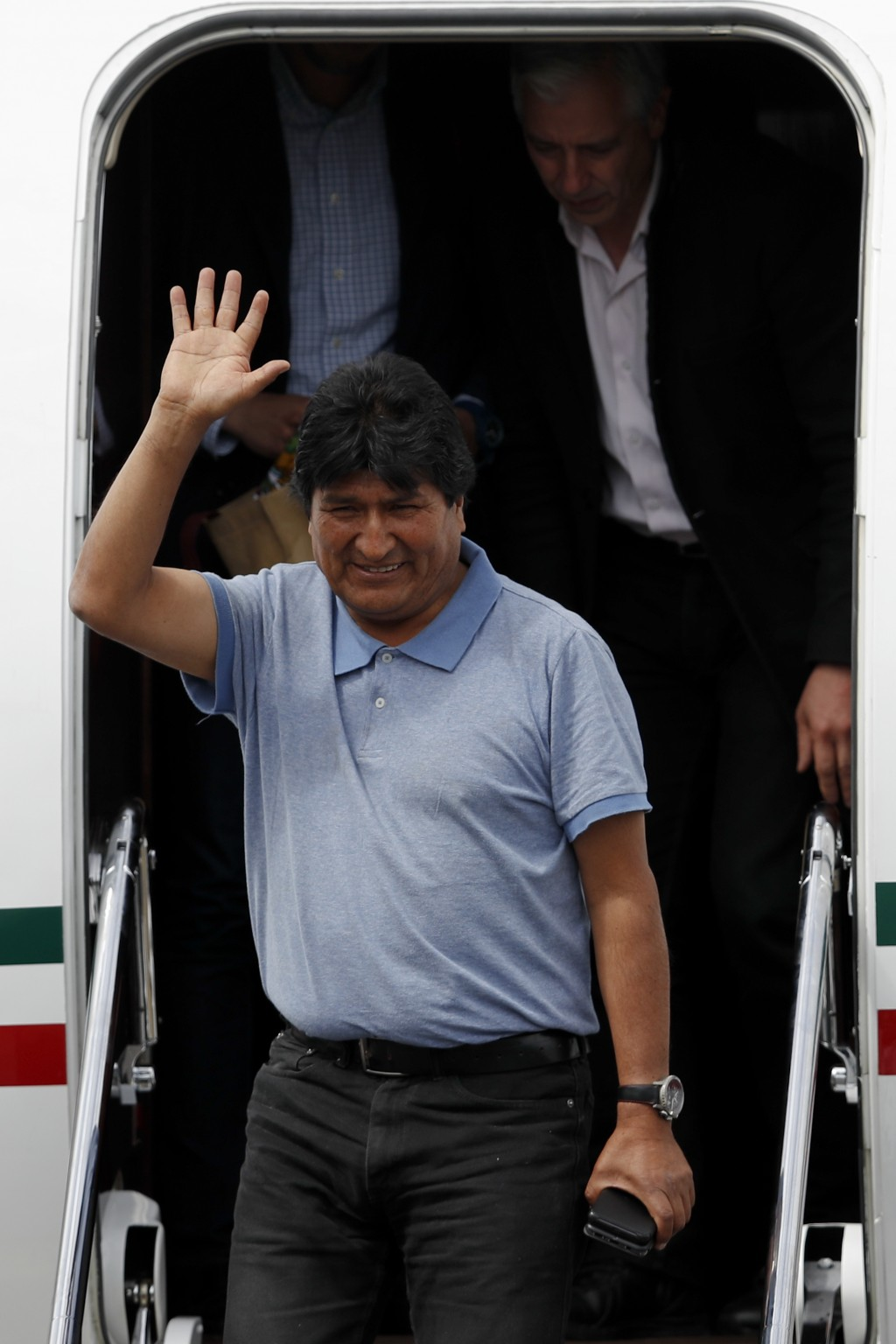 Former Bolivian President Evo Morales waves upon arrival in Mexico City, Tuesday, Nov. 12, 2019. Mexico granted asylum to Morales, who resigned on Nov...