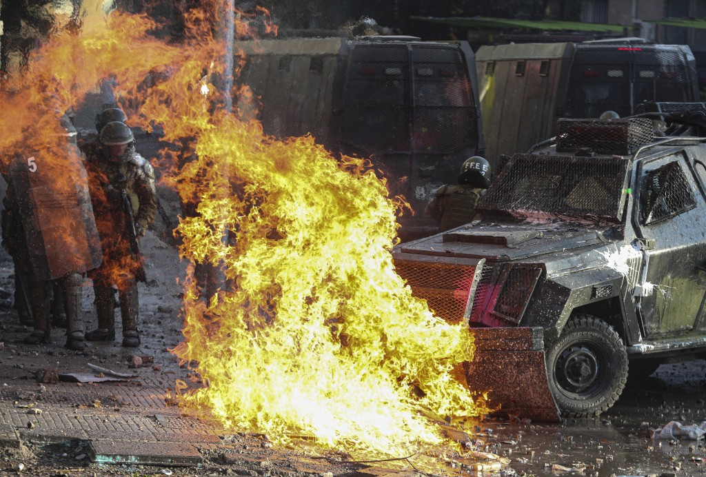 A petrol bomb explodes in front of a police vehicle during clashes with anti-government demonstrators in Santiago, Chile, Tuesday, Nov. 12, 2019. Stud...