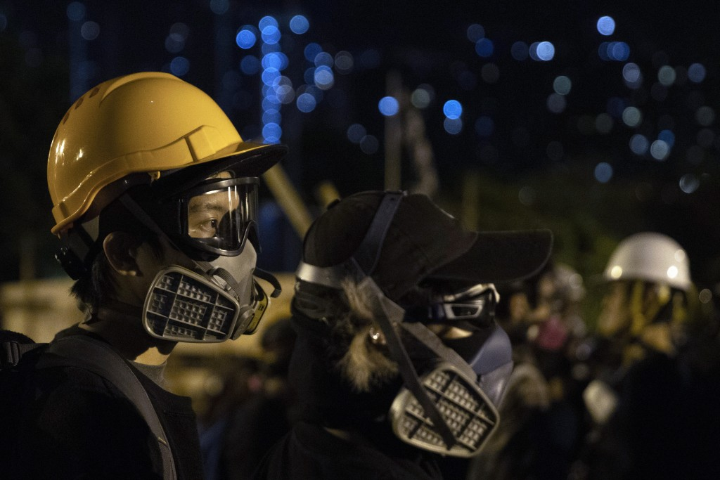 Protesters don gas masks and helmets as they defend a bridge leading into Chinese University of Hong Kong, in Hong Kong, early Thursday, Nov. 14, 2019...