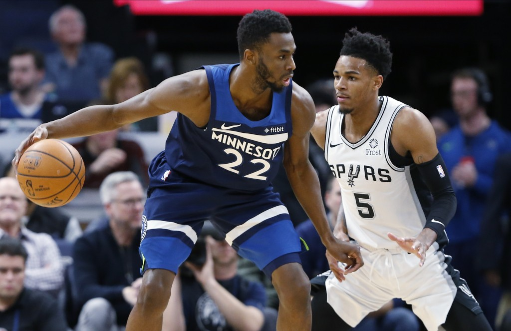 Minnesota Timberwolves' Andrew Wiggins, left, drives around San Antonio Spurs' Dejounte Murray in the first half of an NBA basketball game Wednesday, ...