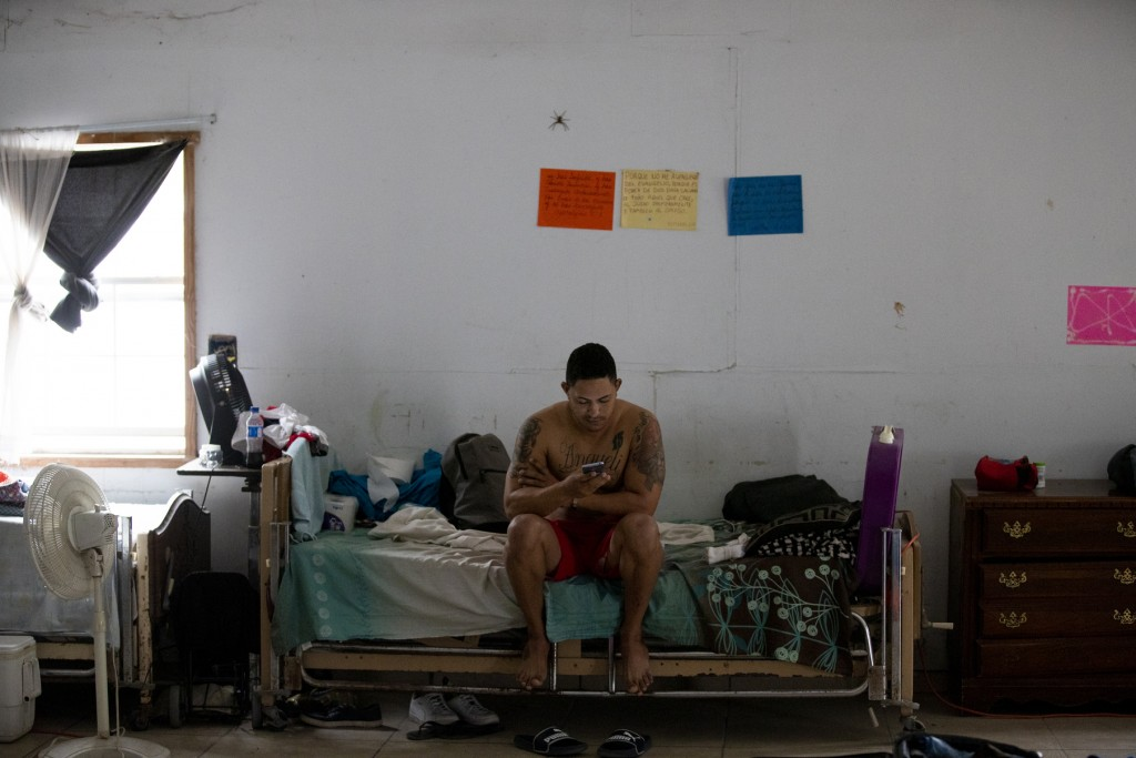 ADVANCE FOR USE SUNDAY, NOV. 17, 2019 AND THEREAFTER- In this Oct. 12, 2019 photo, a Cuban migrant checks his cell phone at a migrant shelter in Reyno...